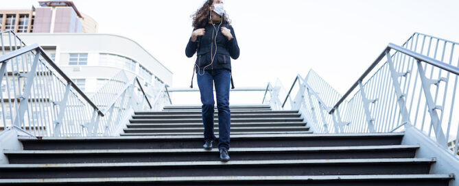 Caucasian woman out and about in the city streets during the day, wearing a face mask against covid19 coronavirus, walking down stairs